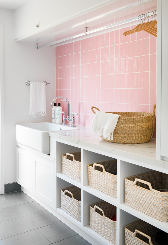 """With countless hours of doing the laundry the norm in this household, Victoria thought she'd add a splash of her favourite colour to the space. Aglow with handmade Manuel gloss tiles in Rosa from Di Moda Collective, the pink splashback injects a modern edge to classic fixtures, including a butler single bowl sink and 'Nicolazzi' sink mixer from Reece. Below the bench, pull-out baskets from West Elm keep the surfaces neat. """"Theoretically everyone has their own basket, which I fill with clean clothes and they put away – but the system needs a little more practise,"""" says Victoria with a laugh."""