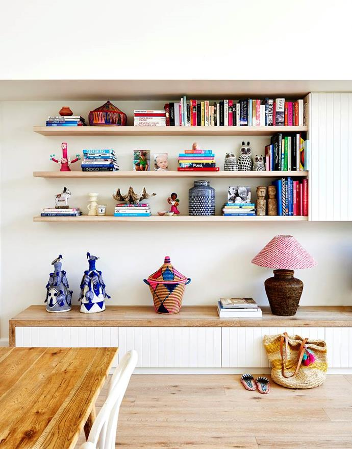 "Custom shelving and cabinetry in the living/dining area of this [colourful Byron Bay home](https://www.homestolove.com.au/coastal-cottage-byron-bay-20442|target=""_blank"") showcases books and homewares, while drawers underneath hide all the toys!"