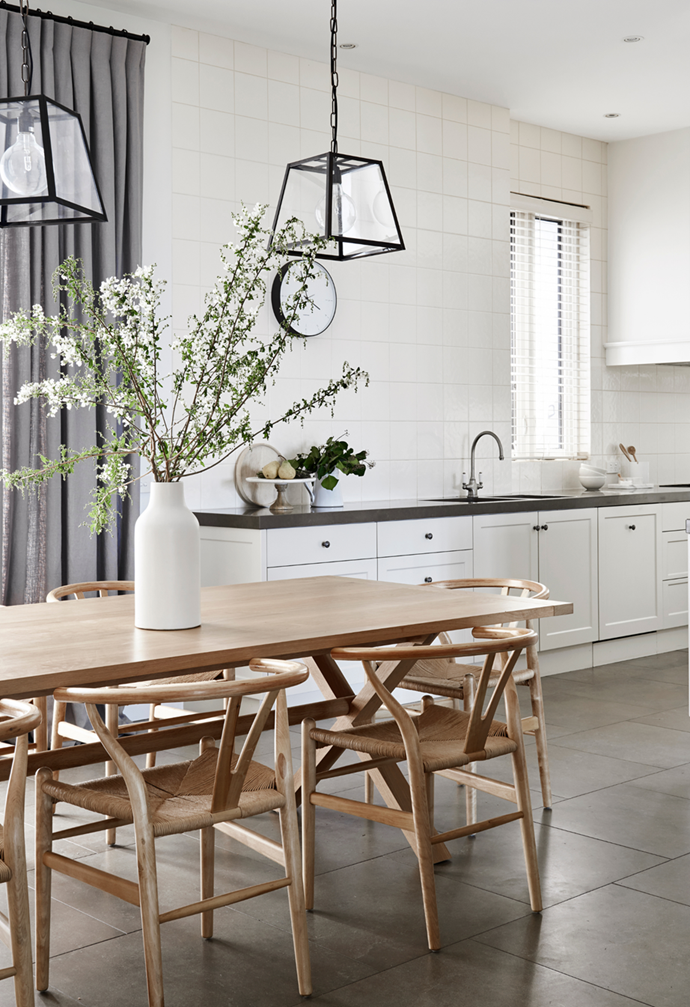 """Showcasing a roomy galley-style kitchen featuring inky stone benchtops and white Shaker-style cabinetry, the cooking and casual Hamptons-style dining zone in this [stylish country home on the Mornington Peninsula](https://www.homestolove.com.au/stylish-country-home-victoria-22436