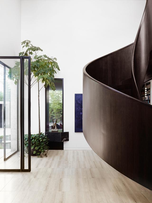"""The serpentine contours of a dark American oak staircase pour through the centre of this [family home](https://www.homestolove.com.au/modernist-mansion-toorak-21774