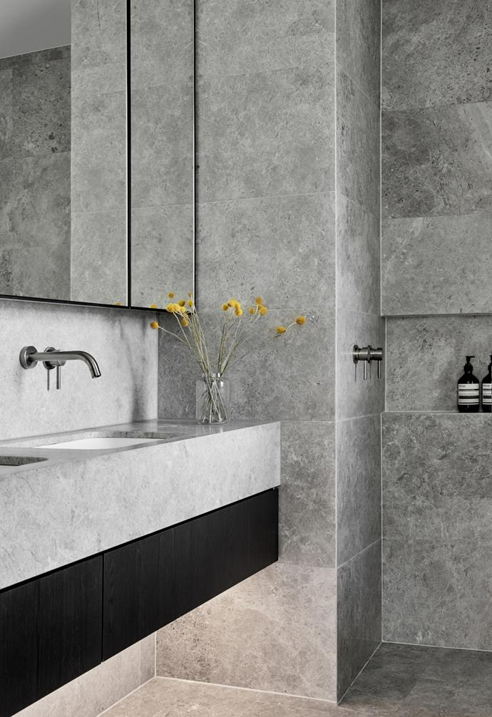 For continuity, the same stone has been used for the floor tiles, wall tiles and vanity top in this sleek bathroom.