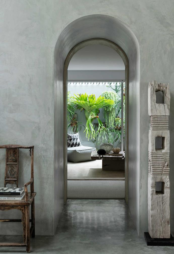 **Main entrance** The chair above sits to the right of the hall table, and the passage leads to the home's media room. Outside the window is a spectacular group of staghorn ferns that form a natural backdrop for the room's aged timber, concrete and organic fabrics.