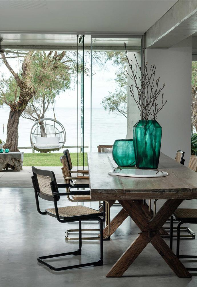 """**Dining** Green has been used to stunning effect with these hand-cut Emerald vases. The custom teak dining table, Breuer chairs and double hanging chair are also from [Empire](https://www.empirehomewares.com.au/