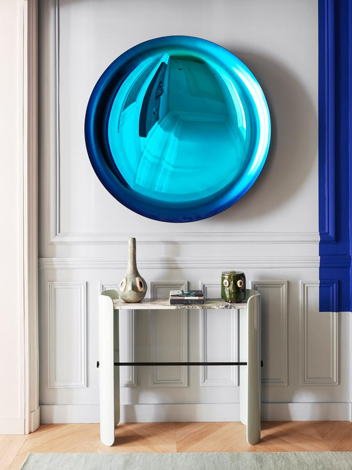 Setting the scene in the entrance hall, a dramatic mirror in moulded and tinted glass by Christophe Gaignon hangs above a 'Belize' console by Le Berre Vevaud. Ceramic vessels on the console by Julien Michaud.
