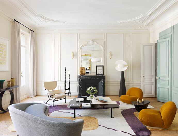 An 'Argan' rug and 'Alma' coffee table, both by Le Berre Vevaud. 'Tre Pezzi' armchair by Franco Albini for Cassina. Italian 1950s sofa. On a Nero Marquina marble table, between two Pierre Paulin 'Pacha' lounge chairs from Gubi, sit candlesticks by William Guillon. 'Monaca' floor lamp by Mauro Fabbro from Alexandre Biaggi. On the fireplace is a Les Gémeaux bronze sculpture by François Stahly. Framed artwork by Myaglo. Iron sculpture beside the fireplace by Sido & François Thevenin. Ceramic dish on the coffee table by Claire de Lavallée.