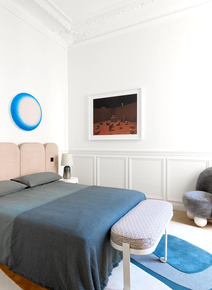 Muted and electric tones of blue merge in the master bedroom, in the form of an 'Assouan' wool rug, a 'Peonia' armchair and a 'Lou' bench upholstered in 'Tribu' fabric from Lelièvre, all by Le Berre Vevaud, as well as the artwork above the bed by Vincent Beaurin. Bed linen from Society Limonta. 'Gigaro' bedside lamp by Charles Zana. Photograph by Marina Gadonneix.