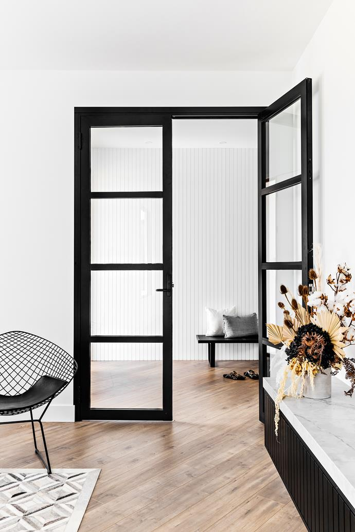 """The formal [living room](https://www.homestolove.com.au/living-room-essentials-3466 target=""""_blank"""" rel=""""nofollow"""") at the front of the home is a vision of monochrome magic, with walls painted in Dulux White on White and steel doors powder-coated in Dulux Colorbond Monument. The cladding in the entryway adds interest and dimension – """"We didn't want an artwork in the entryway so this is a nice alternative,"""" says Veronica – while a rare hint of pattern comes courtesy of the graphic floor rug; try Temple & Webster's Grey Diamond Flat Weave Wool-Blend rug for similar."""