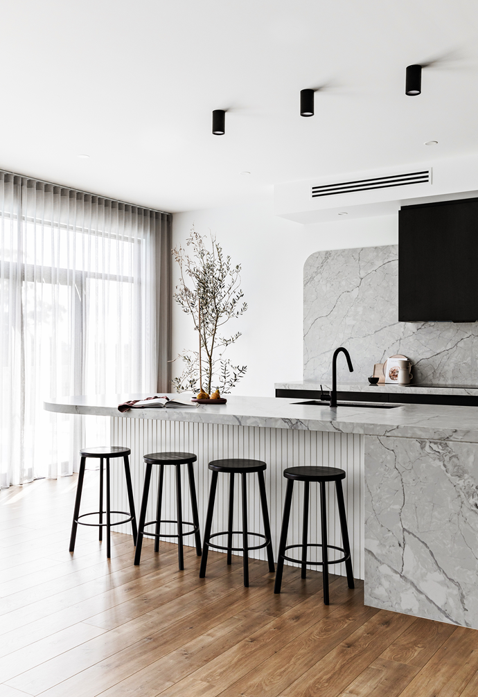 """The hub of the home is also a haven of calm, designed to keep clutter at bay. The star of the space is the island bench, a curvy custom creation by Vision Kitchens & Joinery featuring engineered stone benchtops – Talostone in Super White – plus polyurethane VJ panelling below painted in Dulux Vivid White. Shots of black come via the 'James' bar stools from Interior Secrets, Reece 'Mizu Drift' tapware and Schweigen rangehood. Yet the slick space is anything but sterile, with streams of [natural light](https://www.homestolove.com.au/how-to-increase-natural-light-in-home-15836 target=""""_blank"""") and a fragrant olive tree in the corner."""