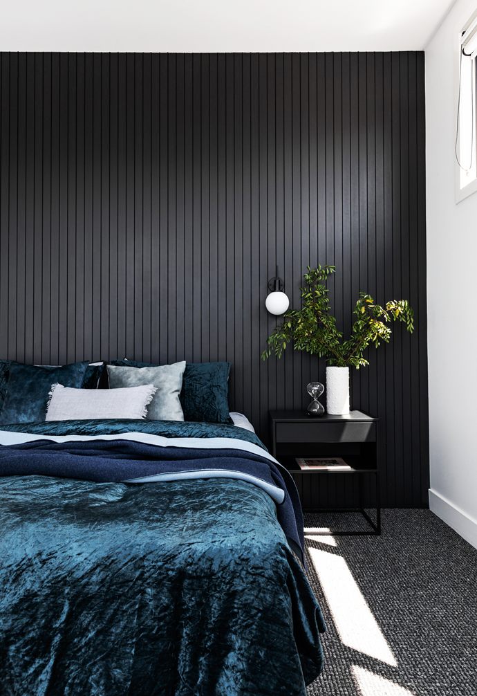 """How to conjure drama, depth and softness all at once? Take notes from Veronica and Mark's bedroom, which centres on a striking panelled feature wall in Dulux Monument. """"We chose it instead of a bedhead,"""" explains Veronica. The dark tones are also countered by luscious teal and navy bedlinen – Morgan & Finch velvet designs from Bed Bath N' Table – plus Beacon Lighting bedside pendants (try the 'Create' style for similar), which lend a dose of contemporary cool."""