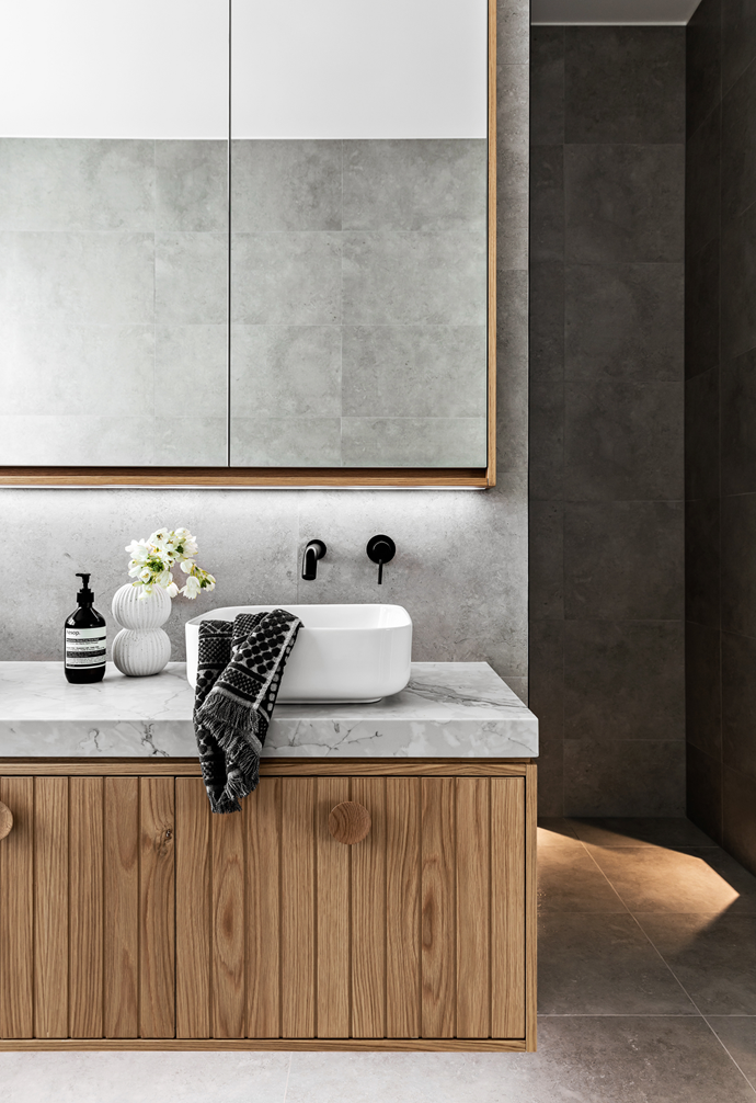 Swathed in natural tones, the main upstairs bathroom  stays true to the couple's clean and simple design ethos. A 'Luna' basin from Caroma sits atop easy-to-clean Talostone and custom-built American oak joinery, while large-format porcelain floor and wall tiles enhance the sense of space. The Reece 'Mizu Drift' tap brings a bolt of black, a recurring theme throughout the home. And the masterstroke: a recessed shaving cabinet offering slimline storage.