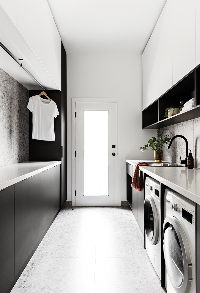 With a super functional layout, the laundry features Polytec Woodmatt Black cabinetry.