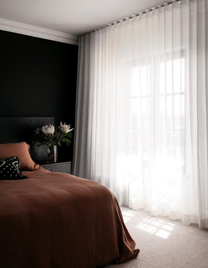 """The layering of earthy tones here are the key to creating a cosy room. This serene master bedroom in an [eclectic and sophisticated home with European influences](https://www.homestolove.com.au/eclectic-and-sophisticated-home-with-european-influences-22343