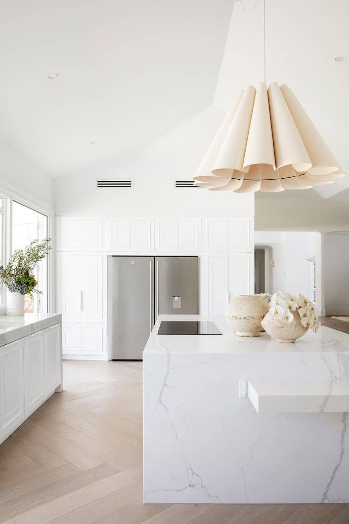 """The kitchen island, which is topped with a 100mm slab of [Talostone 'Calacatta Luxe'](https://talostone.com.au/colours/premium-marble-range/calacatta-luxe-9030/