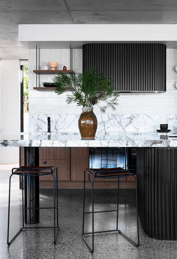 """**Kitchen** """"At 5.4 metres, the island is the main attraction,"""" says Kirsty, perching on a Barbera 'Uccio' stool. It's functional, too, housing the dishwasher, sink, food-prep area and breakfast bar. Honed marble features in the benchtop and splashback. [Billi](https://www.billi.com.au/ target=""""_blank"""" rel=""""nofollow"""") tap. Fabbian 'Lumi Sfera' wall lights, [Caribou](https://caribou.com.au/ target=""""_blank"""" rel=""""nofollow""""). [Falmec](https://www.falmecau.com/ target=""""_blank"""" rel=""""nofollow"""") rangehood clad in Black Japan-stained silky oak battens."""
