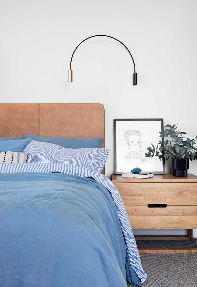 """**Main bedroom** Kirsty and Ben's bedroom opens to a balcony with views of the Brisbane River. Flat leather bedhead, [Fenton & Fenton](https://www.fentonandfenton.com.au/ target=""""_blank"""" rel=""""nofollow""""). Estiluz 'Volta' wall light, [Lumen8](https://lumen-8.com.au/ target=""""_blank"""" rel=""""nofollow""""). Solaris side table, [Satara](https://www.satara.com.au/ target=""""_blank"""" rel=""""nofollow""""). Bed linen, [Society Of Wanderers](https://societyofwanderers.com/ target=""""_blank"""" rel=""""nofollow""""). Quilt cover, [I Love Linen](https://www.ilovelinen.com.au/ target=""""_blank"""" rel=""""nofollow""""). Artwork by Justina Blakeney."""