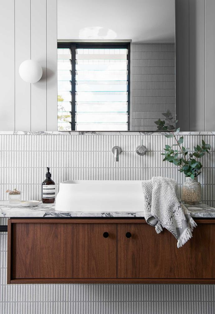 """**Ensuite** Kirsty and Ben left out a wall between their bedroom and ensuite to keep the space """"light-filled and functional"""". Inax 'Yohen' mosaic wall tiles from [Artedomus](https://www.artedomus.com/ target=""""_blank"""" rel=""""nofollow""""), installed by [Korpac Tiling](https://www.instagram.com/korpactiling/?hl=en target=""""_blank"""" rel=""""nofollow""""). Omvivo 'Latis' basin, [Reece](https://www.reece.com.au/ target=""""_blank"""" rel=""""nofollow""""). Fabbian 'Lumi Sfera' wall light, [Caribou](https://caribou.com.au/ target=""""_blank"""" rel=""""nofollow"""")."""