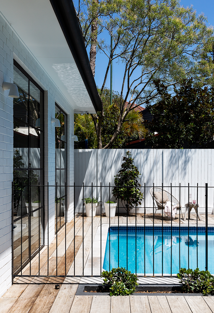 A classic iron fence and timber decking surround the family-friendly pool in the back garden.