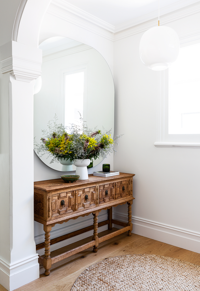 A Jacobean-era console from an antique store in New Zealand pairs with an MCM House mirror in the entry.