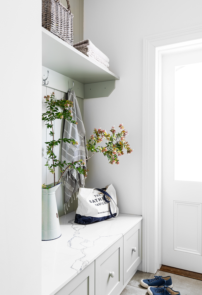 """Calm tones continue with cabinetry in Dulux Waltzing and a 'Statuario Maximus' marble bench seat top from Caesarstone in the regularly used [mud room](https://www.homestolove.com.au/mudroom-design-6620
