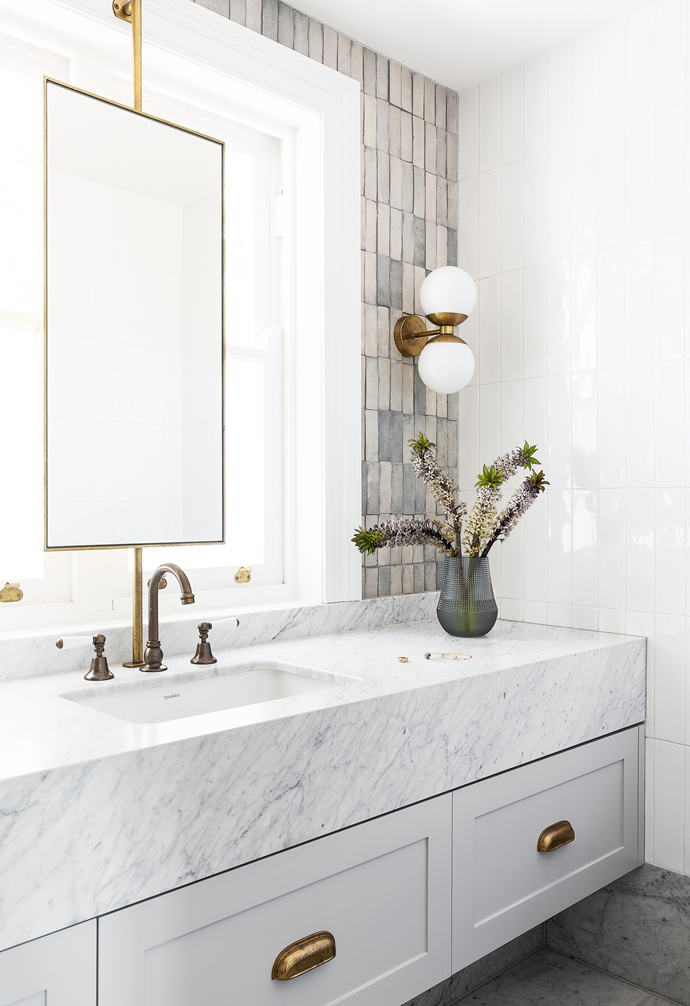 """""""We mixed muted tones and unpolished brass, knowing it will patina and age,"""" say interior designers Smith + Levine, who designed swivelling mirrors to work around the existing window placement."""