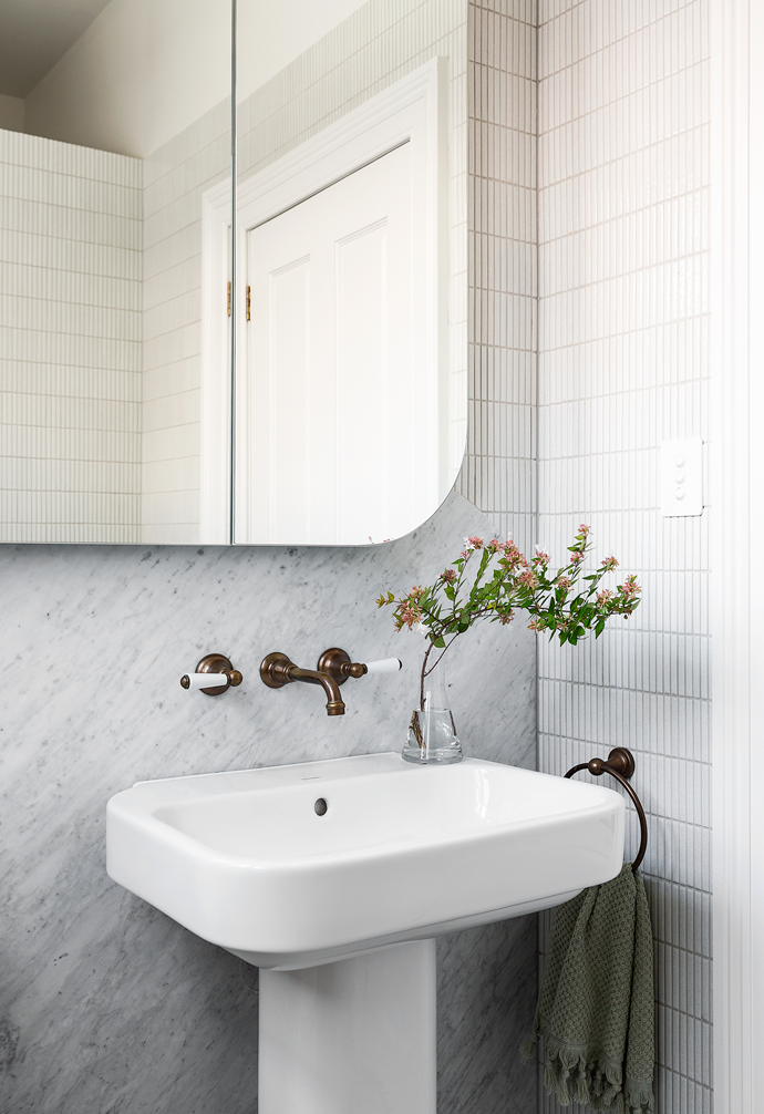 Curves appeal in this petite yet chic space, with a custom mirror designed by Smith + Levine and a 'Happy D.2' pedestal washbasin from Duravit. Teranova 'Crackle' finger tiles, Carrara marble from CDK Stone and aged brass 'Olde English' fittings from Astra Walker provide the backdrop.
