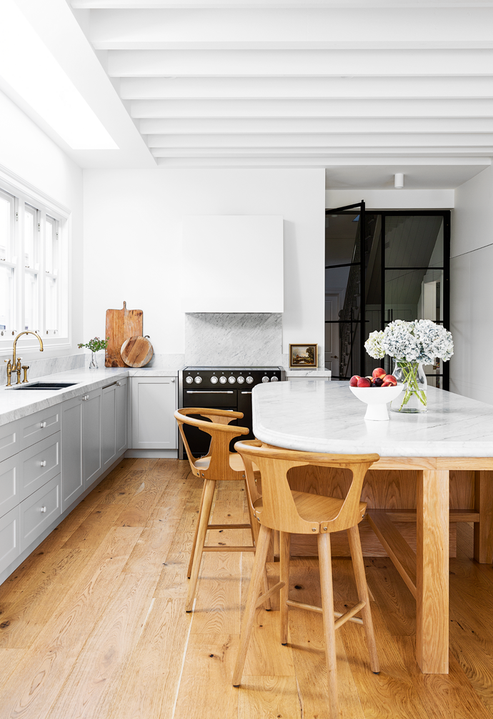 """A seamless design by Smith + Levine has a bespoke island as its centrepiece. """"It has different details and hardware to the rest of the kitchen and is intended to feel like a custom piece of [timber furniture](https://www.homestolove.com.au/decorating-with-timber-furniture-4297