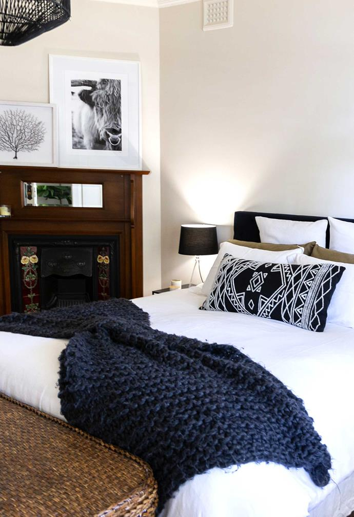 The master bedroom boasts a mix of plush textures from the seagrass storage bench at the foot of the bed, to the thick knitted throw on the bed itself.