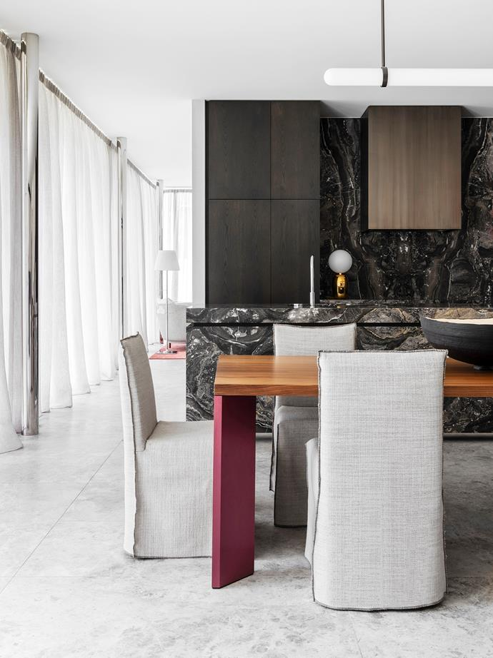 """Owners Luke and Alex Skurrie with their four young children. """"I wanted a sturdy dining table but didn't want it to feel like a boardroom, so we paired it with linen chairs,"""" says designer Brem Perera of the Cassina 'Ordinal' table from Space and Gervasoni 'Ghost 23' dining chairs from Anibou. 'Shinki' bowl by Makiko Ryujin. Arabescato Grigio marble from Signorino covers the kitchen island. 'Scandal' pendant light by Articolo. 'Aballs' table lamp from Ke-Zu."""
