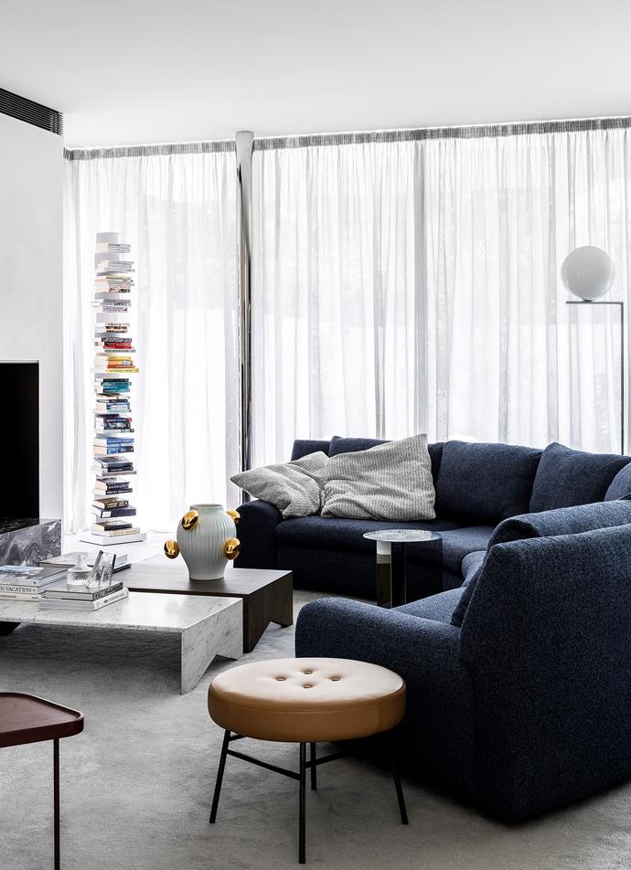A 'Ptolomeo' bookcase and Arflex 'Ben Ben' sofa, both from Space, shape the living room. 'Memphis' coffee tables from Jardan. Moooi vase from Space. Hay 'Slit' table from Cult. Ligne Roset 'Ilot' low stool from Domo. 'IC' floor lamp from Euroluce. Custom rug from The Rug Establishment.