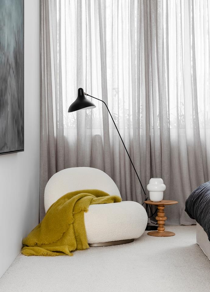The master bedroom is enhanced with a serene palette of ink and soft grey. Gubi 'Pacha' lounge chair from Cult. Ligne Roset 'Kuf' side table, 'Propolis' vase and mohair throw, all from Domo. DCW éditions 'Mantis' floor lamp. Artwork by Zarah Cassim.