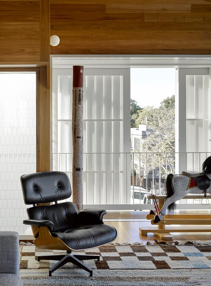 An Eames lounger from Inner Space is positioned near a rocking horse for the owners' grandchildren. Pom Pom rug, Jardan. The wall cladding and floorboards are made from blackbutt.