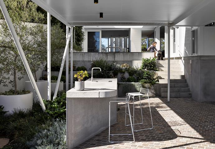 Equipped with a concrete bench and Brodware mixer, the outdoor kitchen is in one of the home's undercrofts. Hay 'Hee' stools, Cult. Planters, Quatro Design. Pavers, Eco Outdoor.