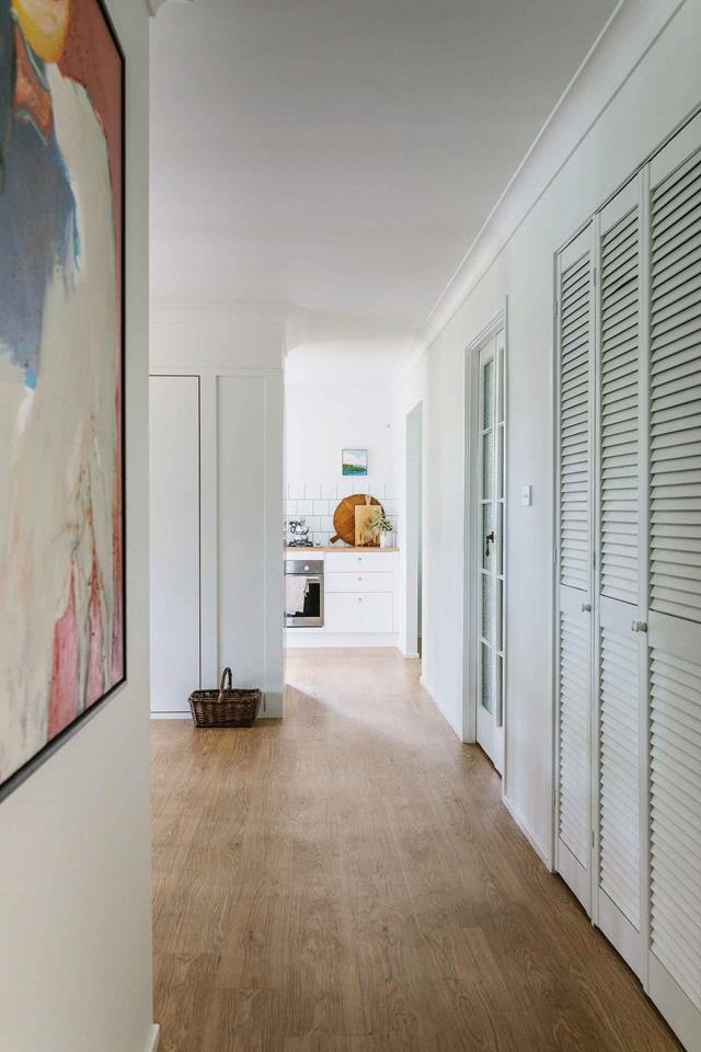 """The hallway in this [Byron Bay home](https://www.homestolove.com.au/diy-home-renovation-12290 target=""""_blank"""") has been beautifully revamped with vinyl plank flooring and newly painted louvre cupboards."""