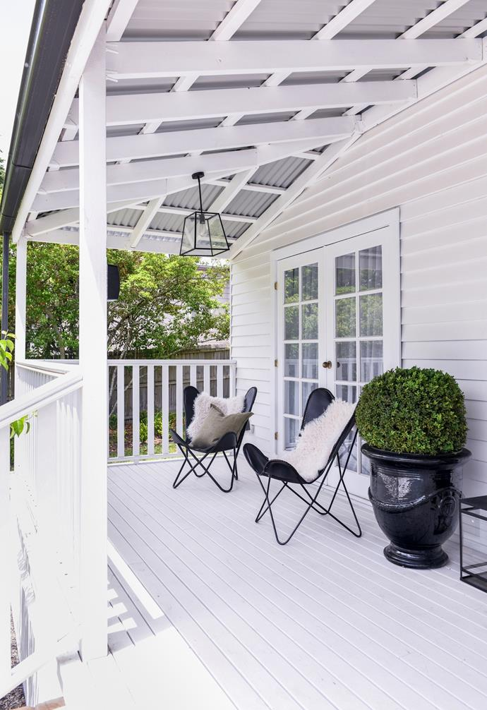 """Black leather butterfly chairs and a light from Beacon Lighting in contrast with the [white home's exterior](https://www.homestolove.com.au/white-house-exteriors-21372