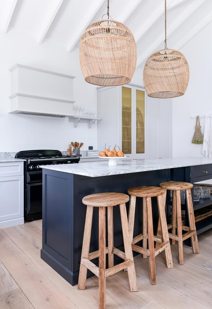 """""""I actually wanted it to blend into the living room and look like a piece of furniture."""" Woven pendants from Inartisan and a dining table and Piana dining chairs from MCM House provide a grounding contrast to the kitchen's refined Carrara marble benchtops and the custom island finished in a deep charcoal tone: Dulux Oolong."""