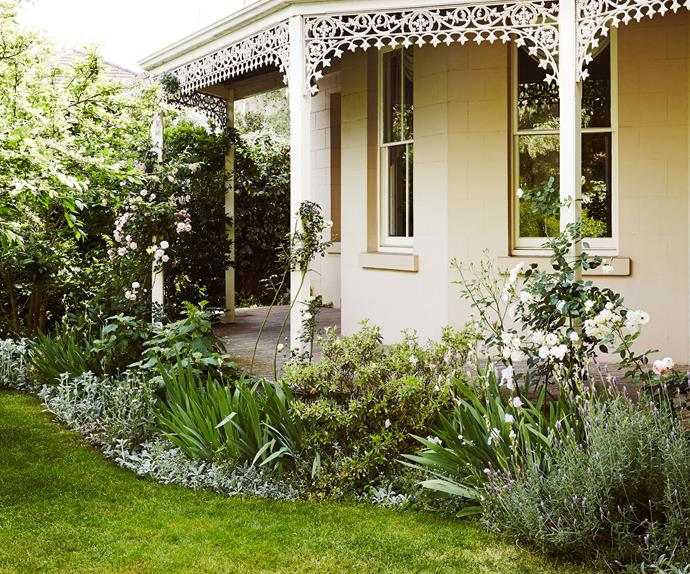 Facade of 19th century home bordered by flower beds