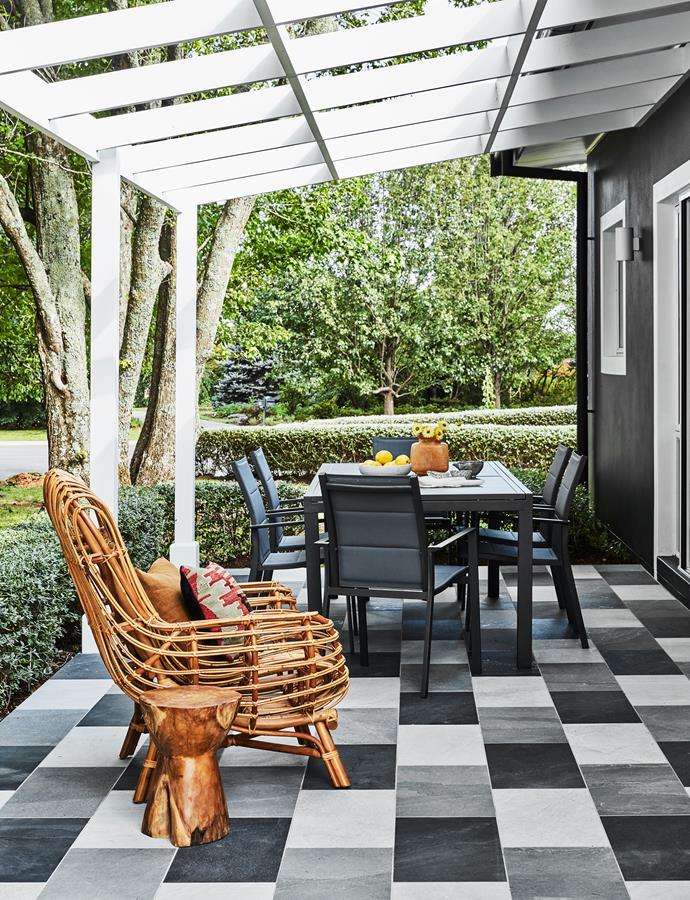 The Maradii cane armchair from MCM House is in prime relaxation position on the patio. X Rock tiles in Nero, White and Grigio, Di Lorenzo Tiles. Outdoor dining setting, Domayne.