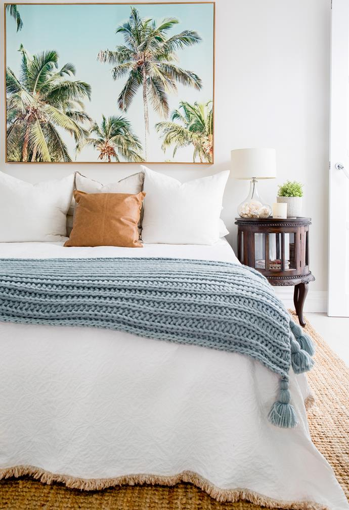 """Previously an [home office area](https://www.homestolove.com.au/home-office-ideas-13393 target=""""_blank""""), this room was converted into a guest bedroom, complete with its own ensuite and garden access. Crisp white bedlinen, a simple jute rug and palm canvas from Alfresco Emporium inject a coastal vibe, while timber bedside tables from their old home in South Africa add the colonial touch Michelle adores. """"The views from the bed are gorgeous, as there are lorikeet families living in the palm tree directly outside,"""" says Michelle."""