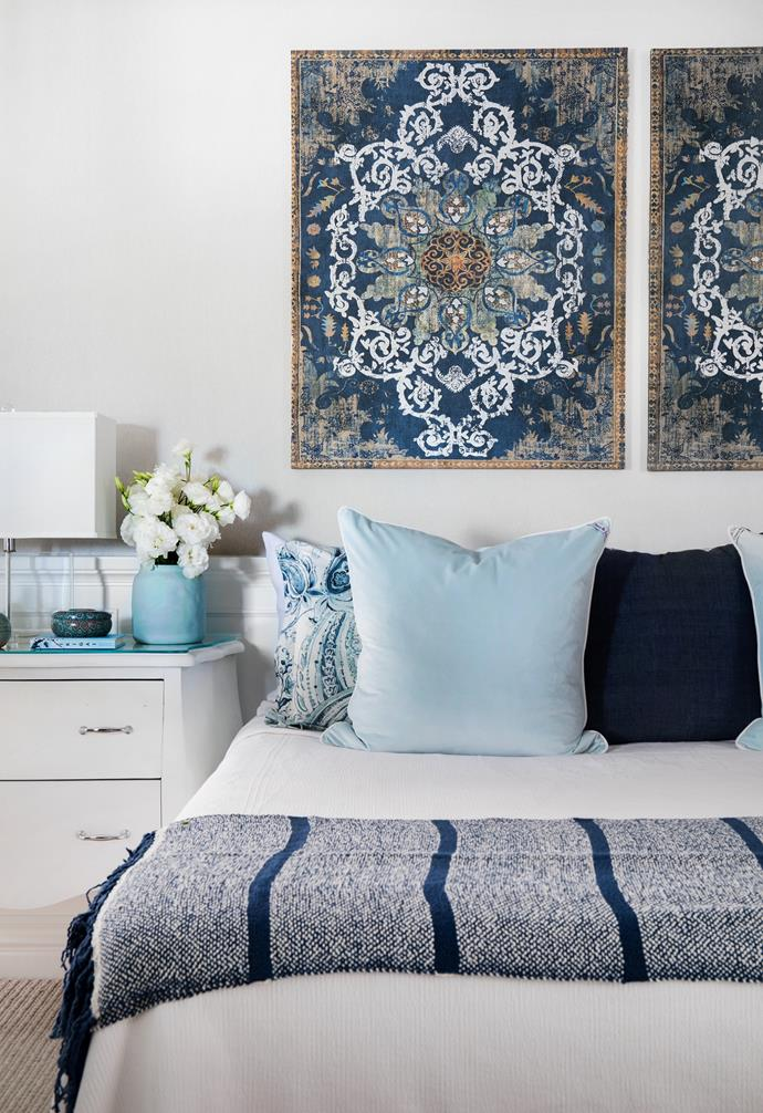 """""""I find shades of blue so serene and relaxing,"""" says Michelle, who continued the coastal palette in the main bedroom with white bedlinen, a navy blue throw from Serena & Lily in America and cushions from Theo & Joe. Above the bed, artwork from C'est Jolie breaks up walls in a grey textured wallpaper from Affordable Decorators. Rather than shop for all new furniture, a simple coating of white paint transformed the bedside tables to tie in with elegant table lamps from That Pretty Market."""
