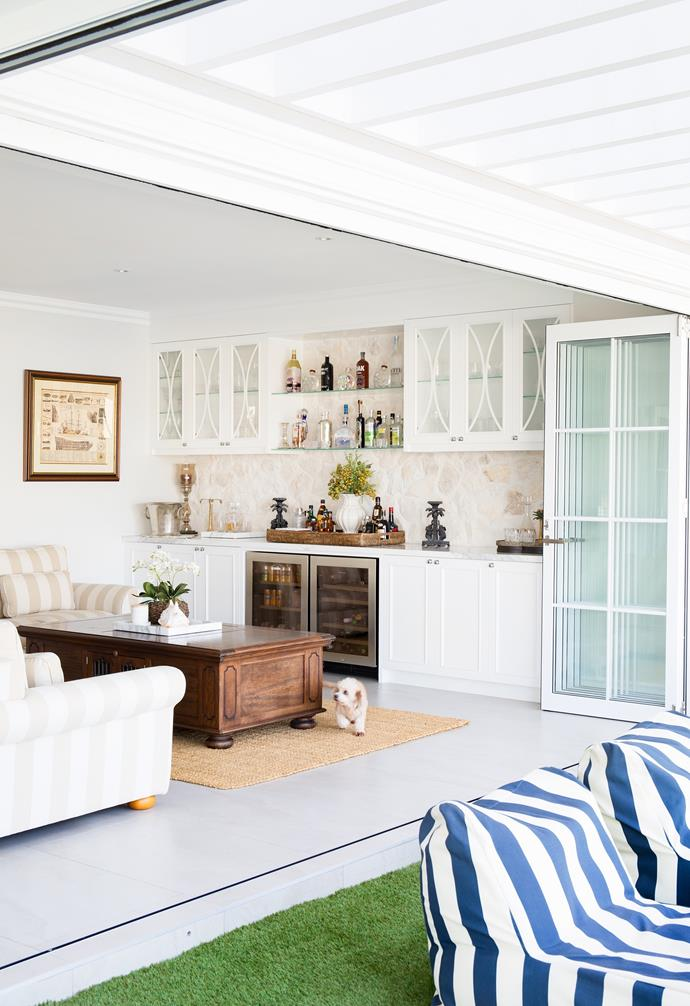 """A bar room, complete with plush sofas, a well-stocked drinks fridge and all the accoutrements for whipping up a sundowner, is ideal for entertaining. """"It was a splurge for the bar splashback to be hand-laid with natural stone, but it really makes the space unique and everyone who visits asks about it,"""" explains Michelle of the tactile finish from 3D Stone. Another considerable cost was retiling the entire ground level, yet the couple haven't regretted the choice of large format Blanco Travertine porcelain tiles from Tile and Stone Gallery, which always remain cool underfoot."""