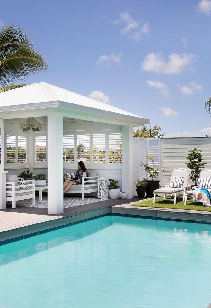 """Originally a basic structure with a thatched Bali-style roof, the gazebo was transformed into a resort-style pool house with a Colorbond roof and semi-enclosed with plantation shutters from Décor Blinds. An all-weather rug anchors the coffee table and a pair of aluminium sofas from Domayne, topped with nautical cushions custom-made with fabric from America. """"The shutters really make the space as they add privacy and can be adjusted to control the amount of sunlight streaming through,"""" says Michelle. """"It's one of my favourite places to read."""""""