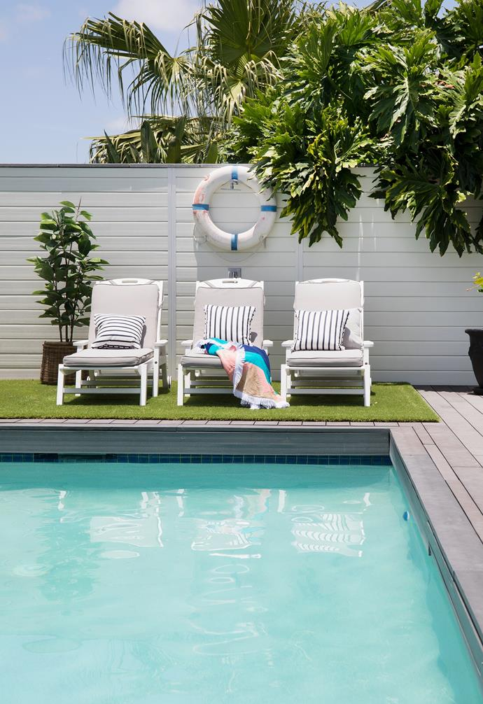 A faux turf rug teamed with Polywood sun loungers provide a perfect spot for everyone to relax poolside. Greenery pops against a new white fence adorned with a decorative life-saving buoy from Coastal Vintage.