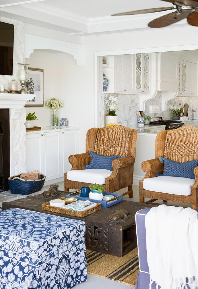 """An addition to the home is an [indoor-outdoor](https://www.homestolove.com.au/indoor-outdoor-flow-21843 target=""""_blank"""") lounge area with bi-fold doors opening up to the pool. A fan from Dune Outdoor Luxuries cools the room in summer. Wicker chairs sit alongside an Ethiopian coffee table to complete the look, while Chinoiserie motifs that appear throughout the house are displayed on the 3 Beaches ottoman, with Serena & Lily cushions echoing pops of blue."""