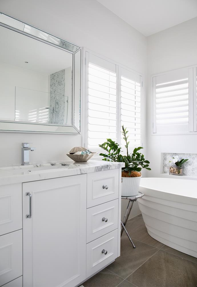A classic white and marble bathroom with a statement Zanzibar gem on a pedestal.