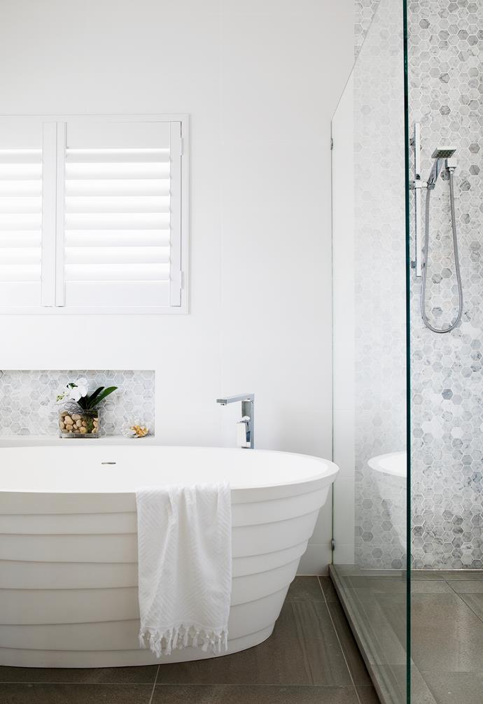 """It was love at first sight when Michelle found the unique freestanding bath that forms a sculptural centrepiece in the main bathroom. """"I wanted to stick with classic grey and white – but with wow-factor,"""" she says. """"The organic curved lines really add a textural feel."""""""