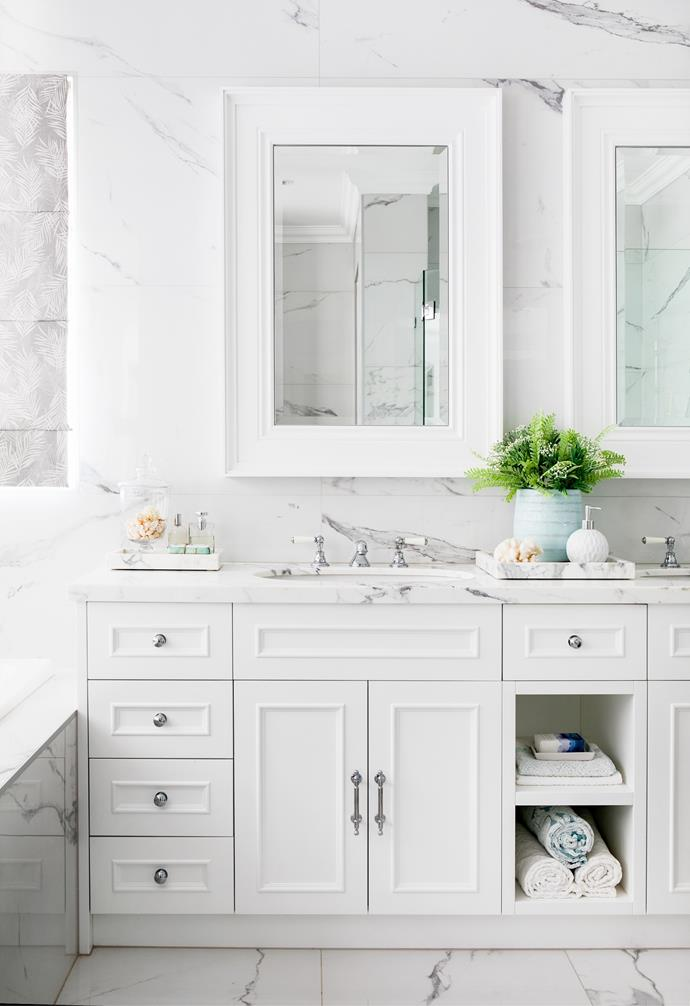 Keeping the finishes timeless and cohesive throughout, a custom shaker-style vanity by FPRR Joinery topped in Statuario marble echoes the winning combination used in  the kitchen. Floor-to-ceiling marble-look tiles from Tile & Stone Gallery enhance the luxe feel, as do twin basins paired with Perrin & Rowe tapware and custom mirrored cabinets above.