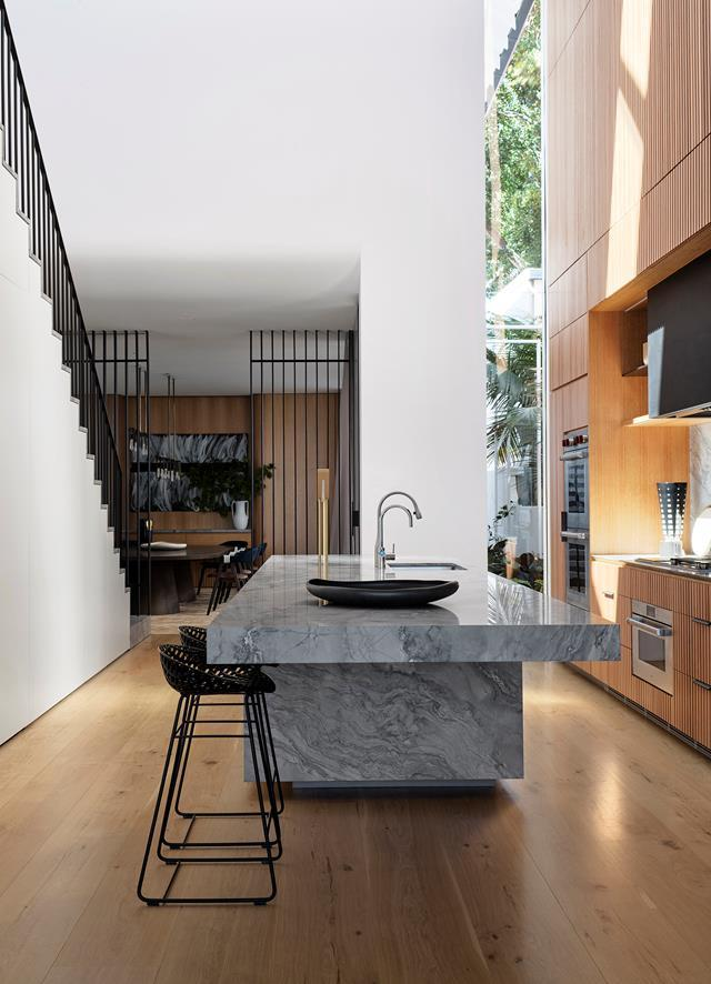 """A thick monolithic island bench grounds this modern kitchen within a [light-filled residence](https://www.homestolove.com.au/modern-three-level-home-sydney-harbour-22160 target=""""_blank"""") conceived by Stafford Architects. A 10-metre void topped with a massive skylight in the centre of the house which drenches the kitchen and adjacent dining area with sunlight."""