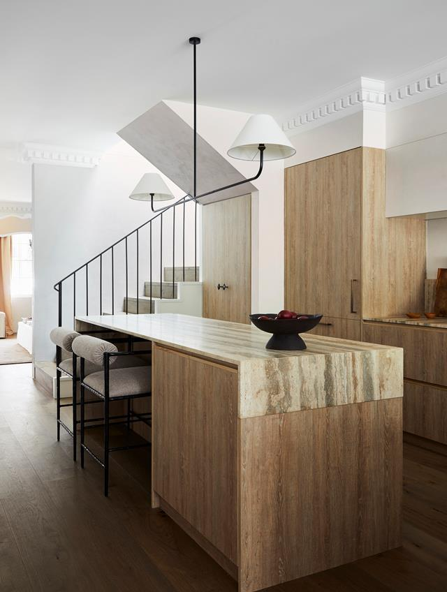 """A bespoke iron pendant light by Phoebe Nicol hangs above the island bench in this [French-inspired home's](https://www.homestolove.com.au/elegant-home-french-inspired-interior-sydney-22184 target=""""_blank"""") timber and limestone kitchen. The island cabinetry is in oak veneer topped with a benchtop in travertine from Gitani Stone."""