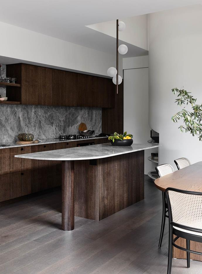 Vertically quarter-cut timber-veneer joinery creates a dark backdrop in this kitchen conceived by architect Maria Danos to provide a dramatic 'aerial perspective'. The curvilinear island bench enables comfortable access around the bench for perching while still allowing a good spatial flow.