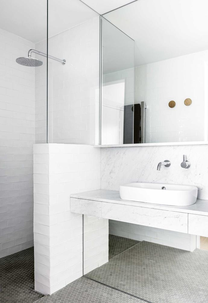 **Ensuite** More tricks here try to compensate for a lack of natural light. Mirrors run above and below the vanity to catch the light from the bedroom and play up the sense of space. A carrara marble splashback and vanity bring the luxe factor.